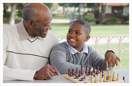 grandfather plays chess with grandson